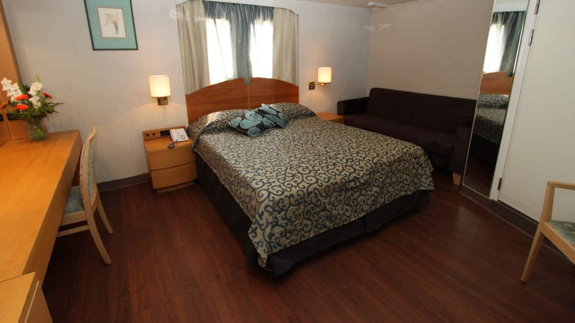 ocean endeavour small ship cabin with a large bed, wood floor, desk and window
