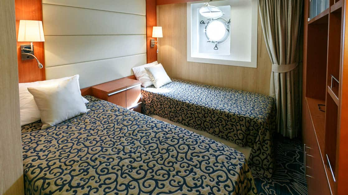 ocean endeavour ship cabin with two beds, a porthole and other furniture