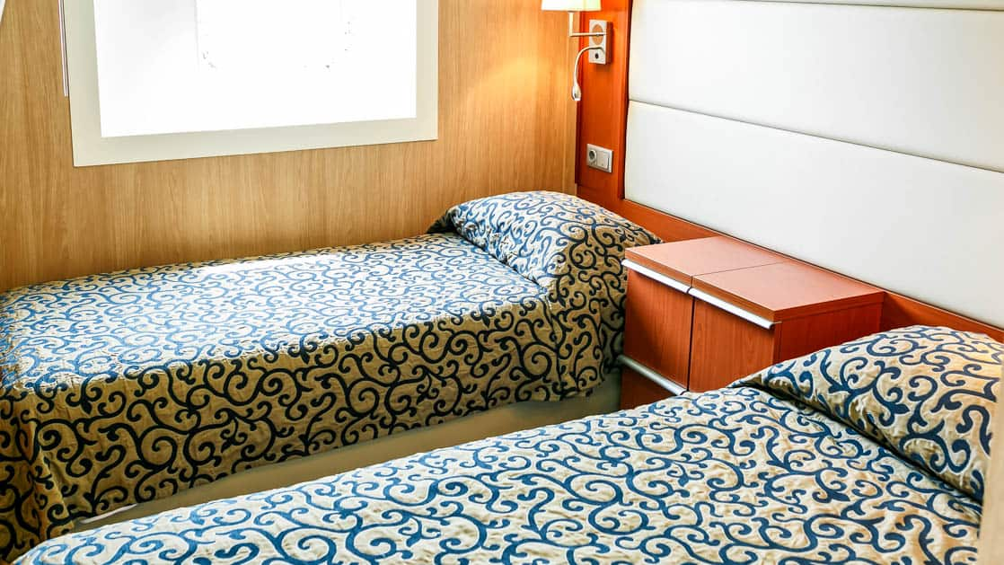 room aboard Ocean Endeavour with 2 beds and a window with the shade down