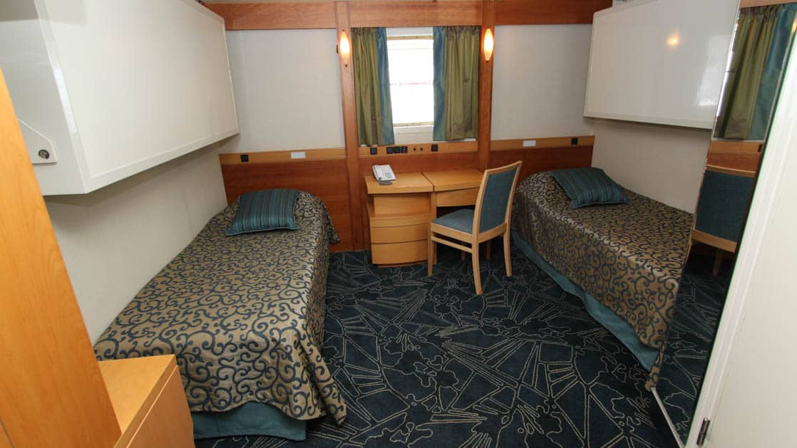 ocean endeavour upper deck double cabin with two beds, a desk window and other furniture
