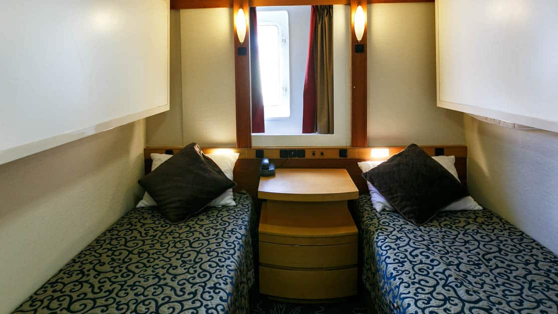 ocean endeavour twin window cabin with two beds, a night stand and a window