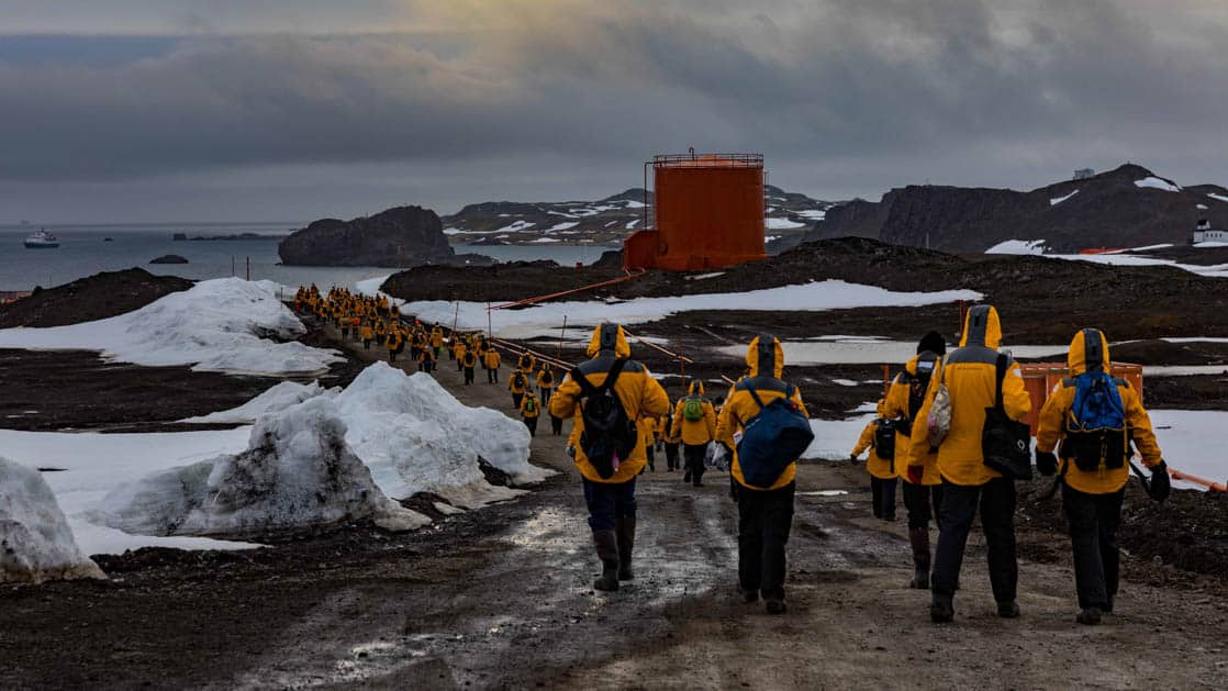 Passengers walking to from their plane to the shore after flying to Antarctica with red tank and shore ahead of them