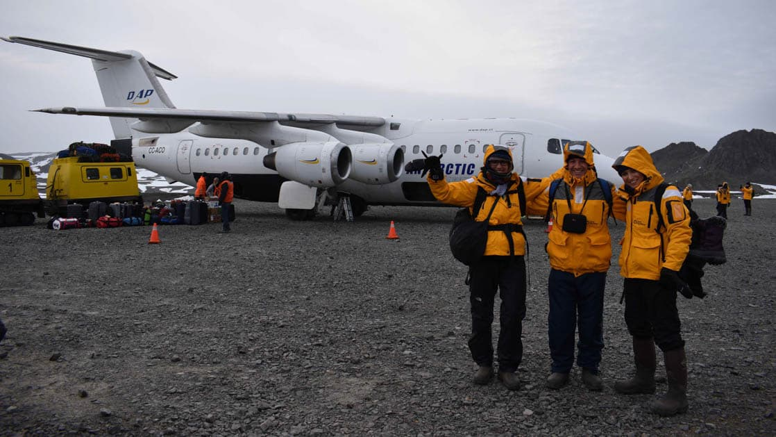 Passengers in Quark yellow jackets Pose in Front of Plane