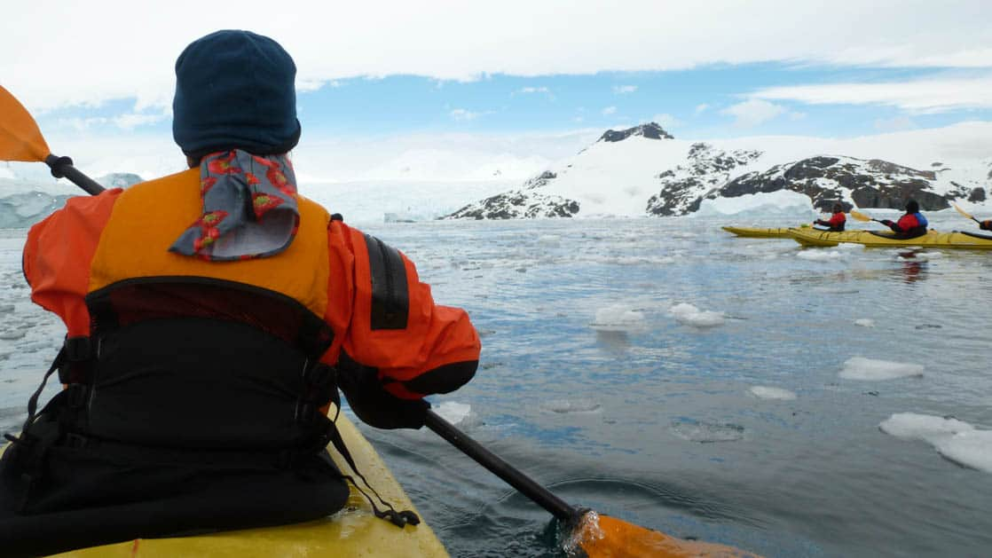 Kayaker paddling with a group of other kayakers among the Antarctica ice