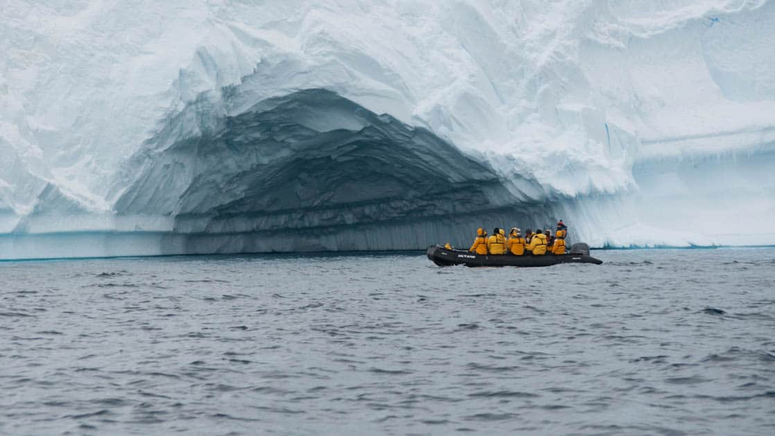 Zodiac filled with Antarctica passengers in yellow jackets in front of an iceberg