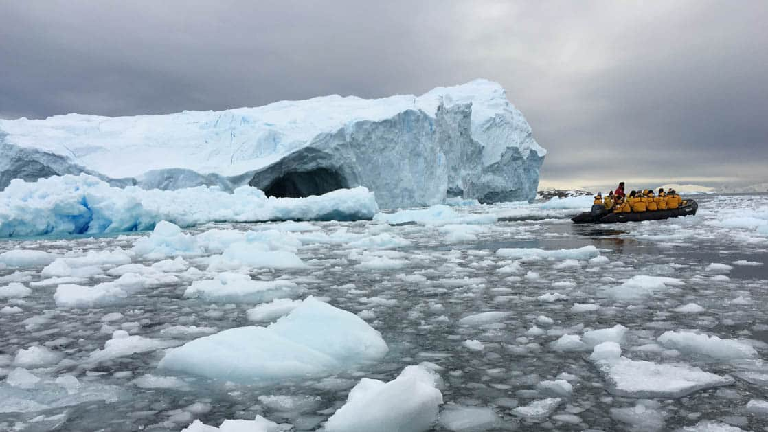 Bergy bits and icebergs surround Antarctica fly cruise passengers in a zodiac