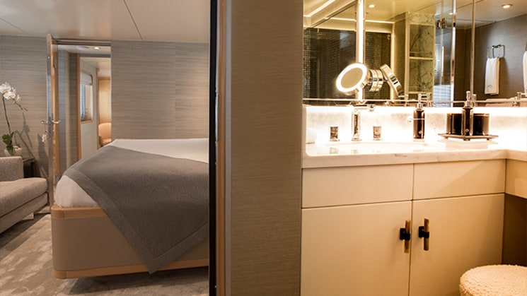 Brightly lit bathroom of category 1 cabin aboard Indonesia yacht Aqua blue, light wooden sink cabinet with mirrors