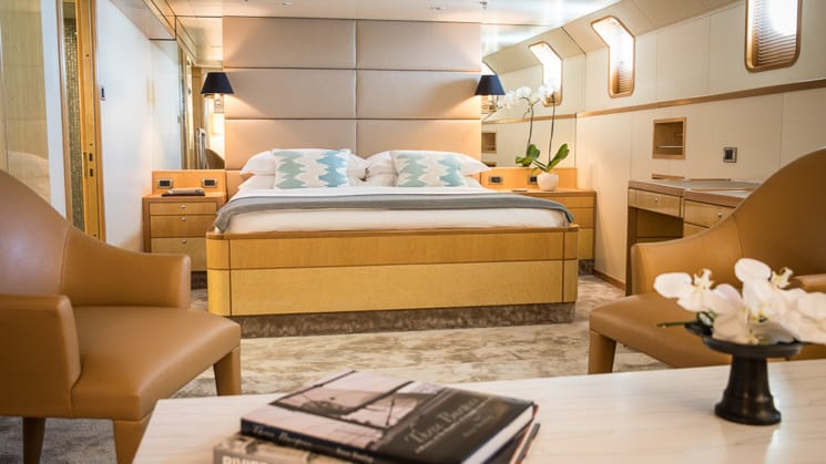double bed against cushioned tan leather headboard wodden accents on the bed frame with tan carpet.