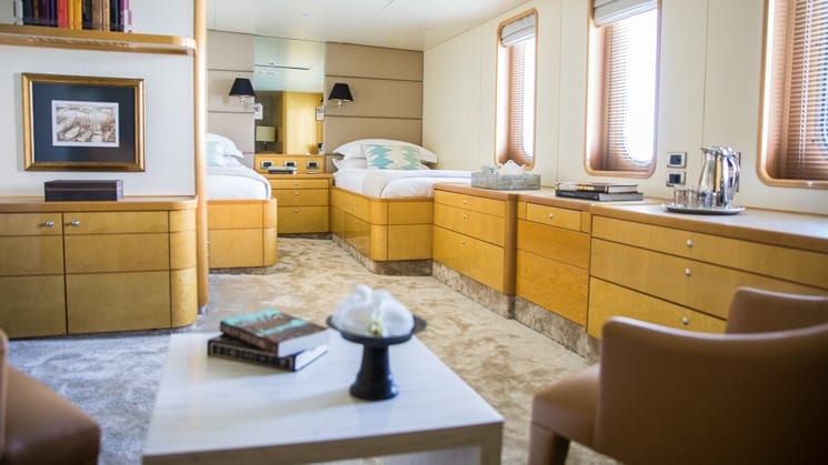 two twin beds with vertical windows, mostly wooden accents and furniture with small seating area, bookshelf, a category 3 cabin board Indonesia yacht aqua blu