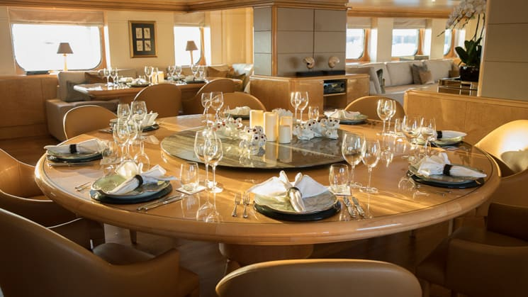 Dinning table aboard Indonesian yacht Aqua Blue, wooden table set with folded white napkins with tan leather chairs