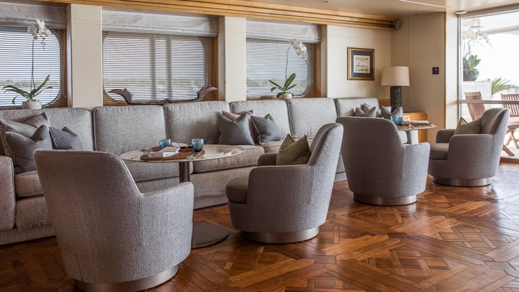 Lounge area aboard Indonesia yacht Aqua Blu wooden flooring below grey blue arm chairs and couches