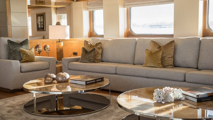 L shaped grey blue couch behind two circular glass coffee tables in the saloon of indonesia yacht aqua blu