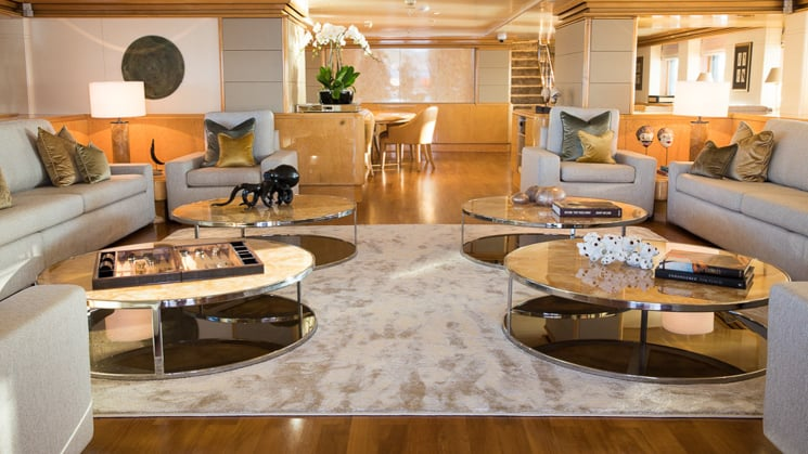 elegant wooden flooring with tan area rugs two circular couches around coffee tables aboard Indonesian yacht Aqua Blu