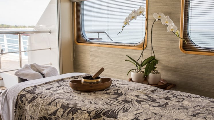 massage table inside spa room of Indonesia yacht aqua ble, a white orchid sitting beside the massage table in front of the windows