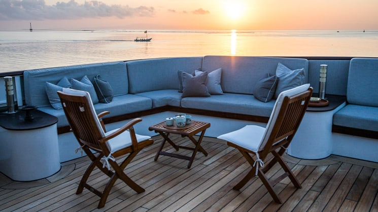 outdoor seating area located on the sun deck of Indonesia yacht aqua blu the sun is setting over the horizon giving the photo a blue tint