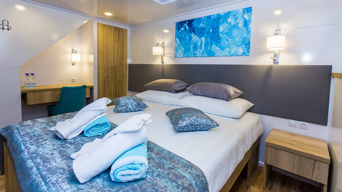 Lower Deck cabin aboard Aquamarin Mediterranean small ship, with double bed, track lighting, wooden bedsie tables & white-&-blue accents.