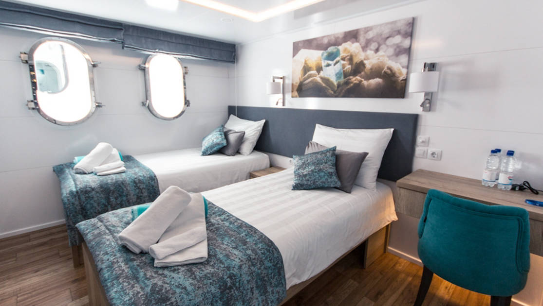 Lower Deck cabin aboard Aquamarin Croatia yacht with 2 twin beds, 2 portholes, desk & chair, with turquoise, silver & white accents throughout.