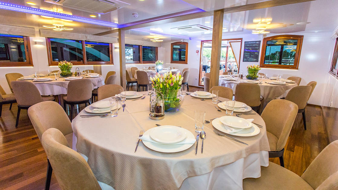 Dining Room aboard Aquamarin Croatia small ship, with small round tables set with white plates, beige tablecloth & tulips in a vase, wooden floor & buffet bar.