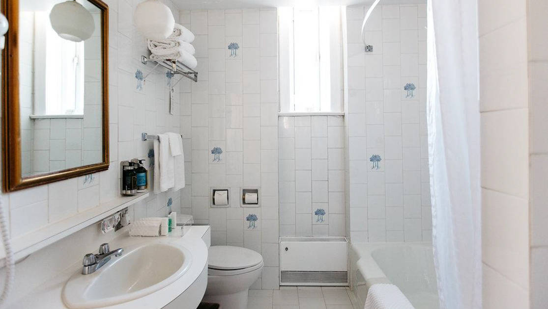 Guest bathroom in all white tile, ceramic sink & toilet, towels on racks, heater & a hanging lantern light at Fort Garry Hotel in Churchill, Canada.