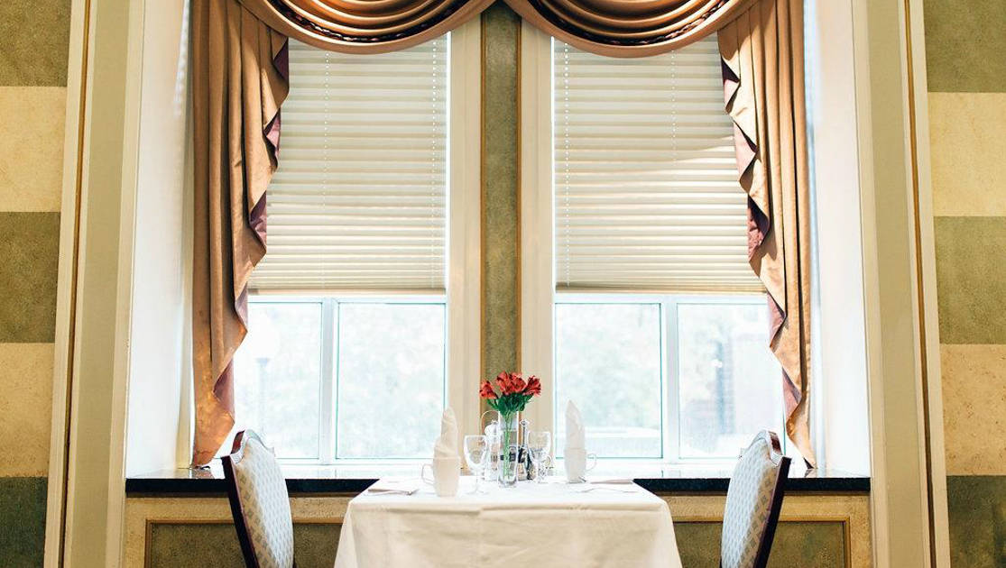 Dining table set for 2 with red flowers in front of a bright double window at Fort Garry Hotel in Churchill, Canada.