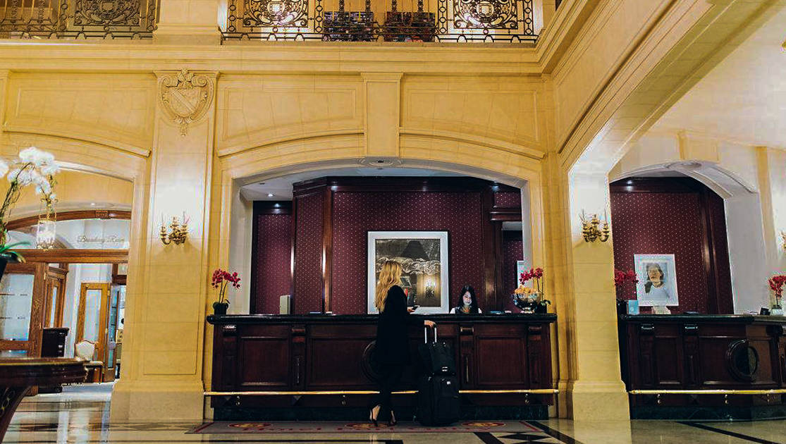 Reception area at Fort Garry Hotel in Churchill, Canada, with a large, castle-like feel, orchids & blonde woman with luggage standing at the mahogany desk.