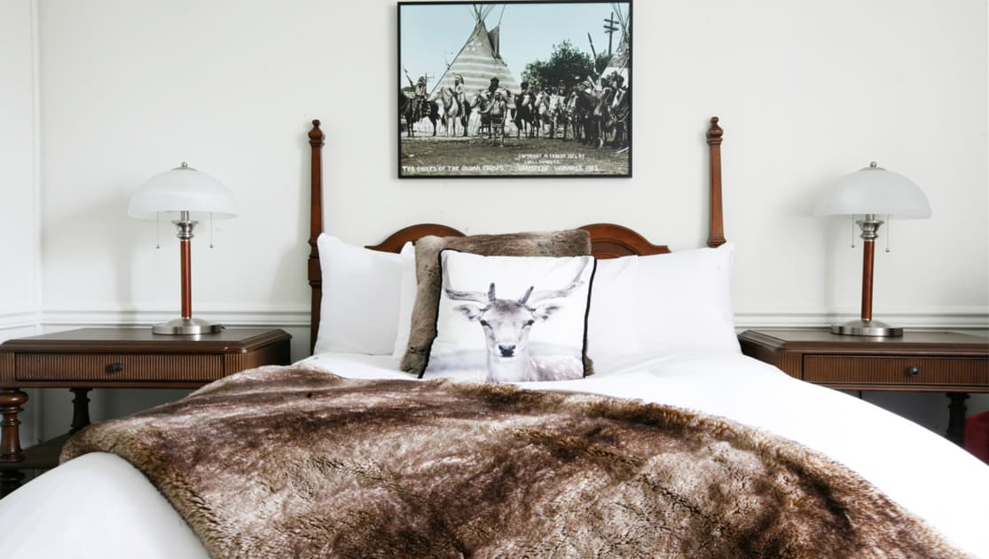 Guest room double bed with white duvet, arctic reindeer-graphic throw pillow, animal skin throw blanket & 2 side tables at Fort Garry Hotel in Churchill, Canada.