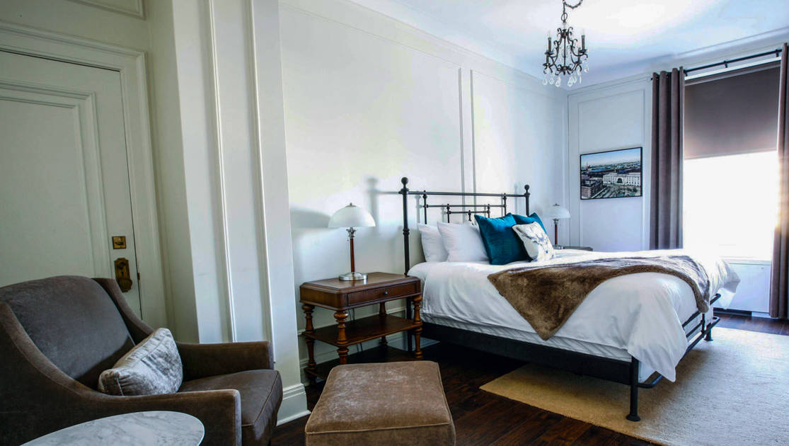 Guest room with double bed, wooden side tables, chandelier, velour chair & ottoman, wooden floors & marble table at Fort Garry Hotel in Churchill, Canada.