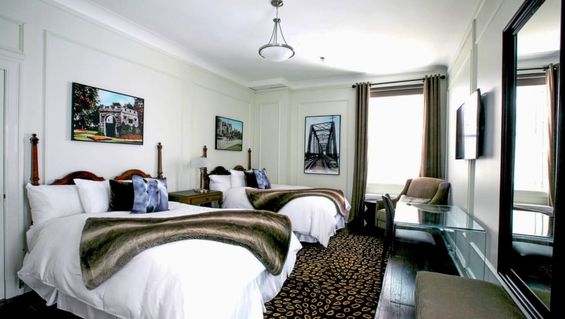 Guest room with two double beds, photographic artwork, TV, glass desk & wooden bedside table at Fort Garry Hotel in Churchill, Canada.