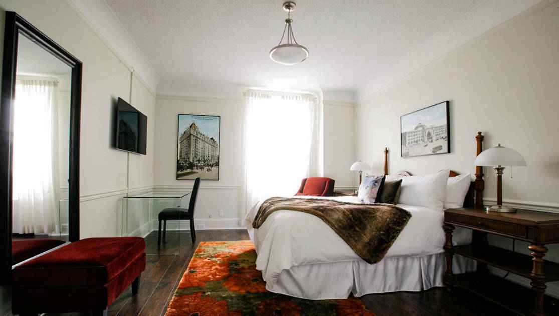 Guest room with wooden double bed & sidetables, lamps, TV, glass desk, chair, velvet ottoman, large mirror & wooden floor at Fort Garry Hotel in Churchill, Canada.