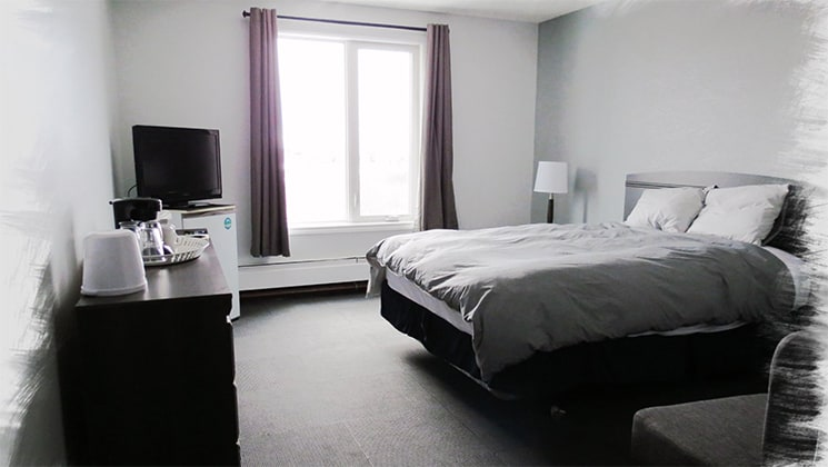 Guest room with double bed covered by a gray duvet, dresser, coffeemaker, mini fridge, TV, chair & window with purple curtains at the Churchill Hotel, Canada.