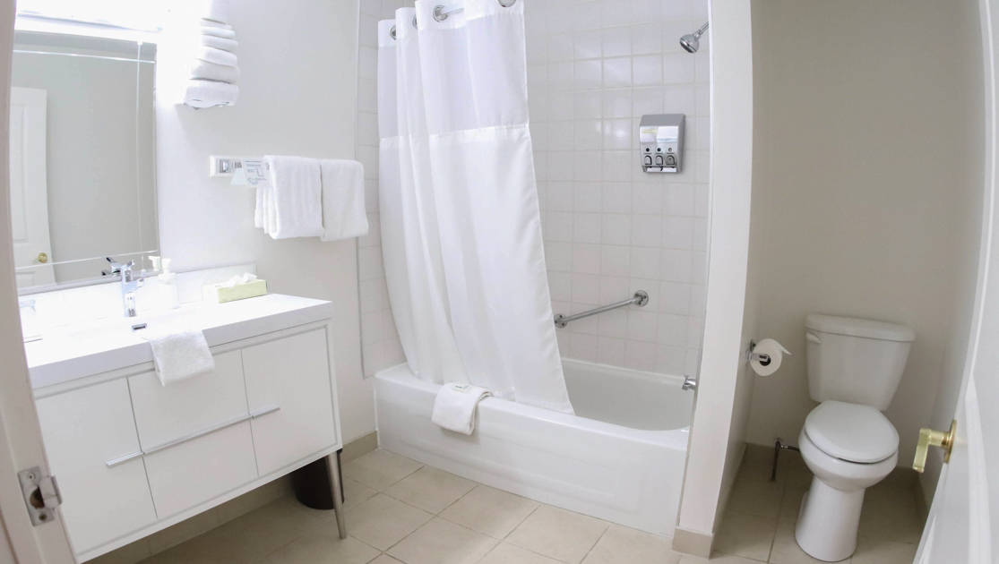 Guest bathroom with white tile and white sink, toilet, shower and towels at the Polar Inn in Churchill, Canada.