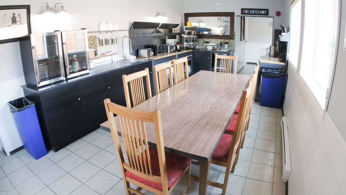 Guest communal kitchen with long wooden table, chairs, countertop refrigerators, microwave, toaster, coffeemakers and counterspace at the Polar Inn in Churchill, Canada.