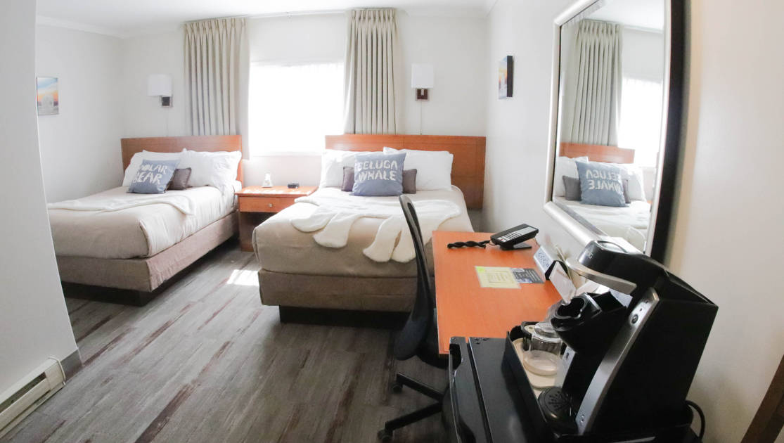 Guest room with two fullsize beds, desk, chair, mirror, mini fridge & coffeemaker at the Polar Inn in Churchill, Canada.