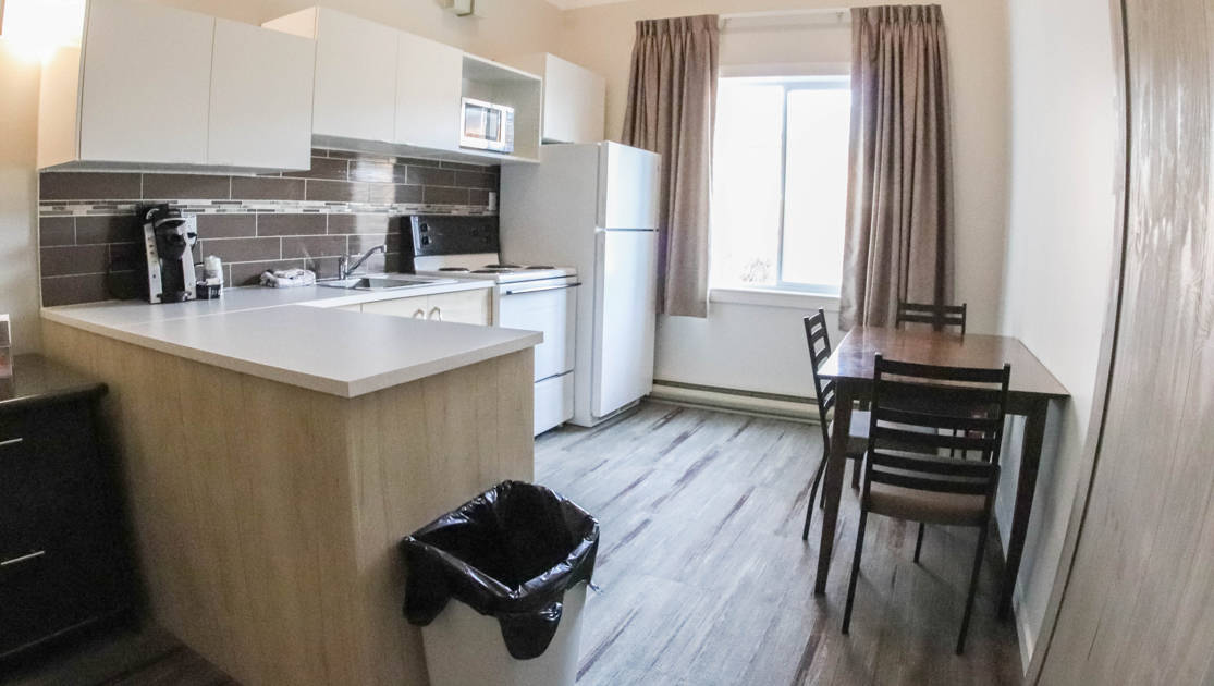 Kitchen with electric stove, sink, counter, refrigerator, cabinets, coffeemaker, table and 3 chairs at the Polar Inn in Churchill, Canada.