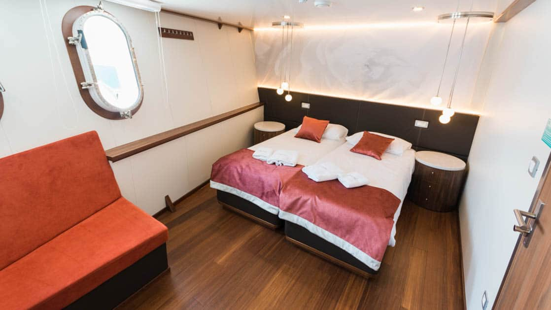 Lower Deck Cabin with porthole, couch, and bed aboard Avangard.