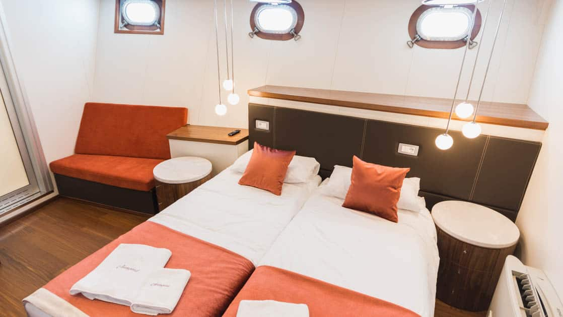 Lower Deck Cabin with 3 portholes, couch, and bed aboard Avangard.