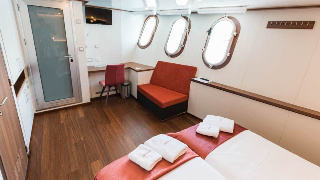 Lower Deck Cabin with 3 portholes, couch, desk, and bed aboard Avangard.
