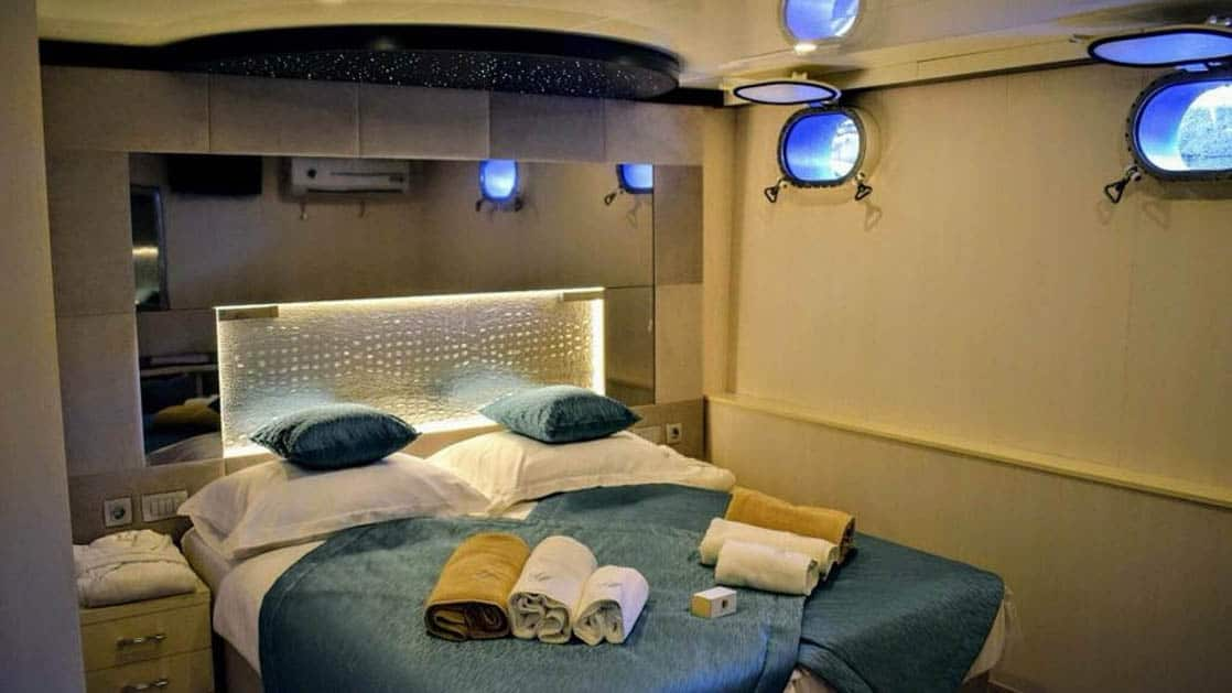 Lower Deck cabin with bed and two portholes aboard Ave Maria