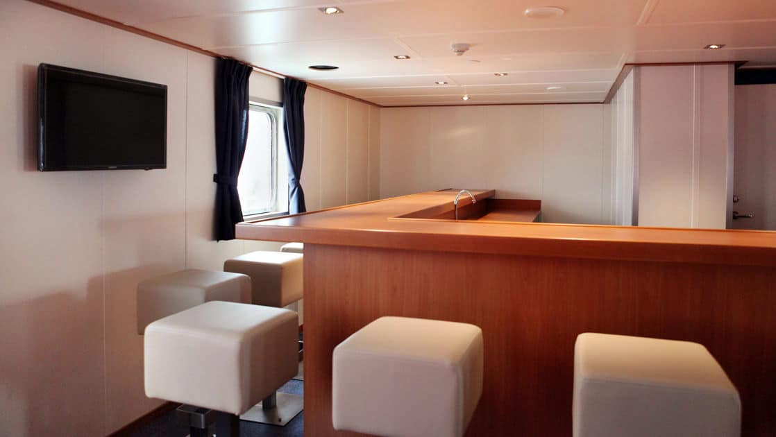 ortelius small ship lounge with a bar and comfortable chairs