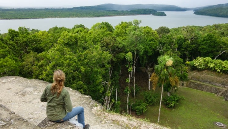 Female sitting atop a mayan temple in tikal guatemala admiring the view over the canopy to the water