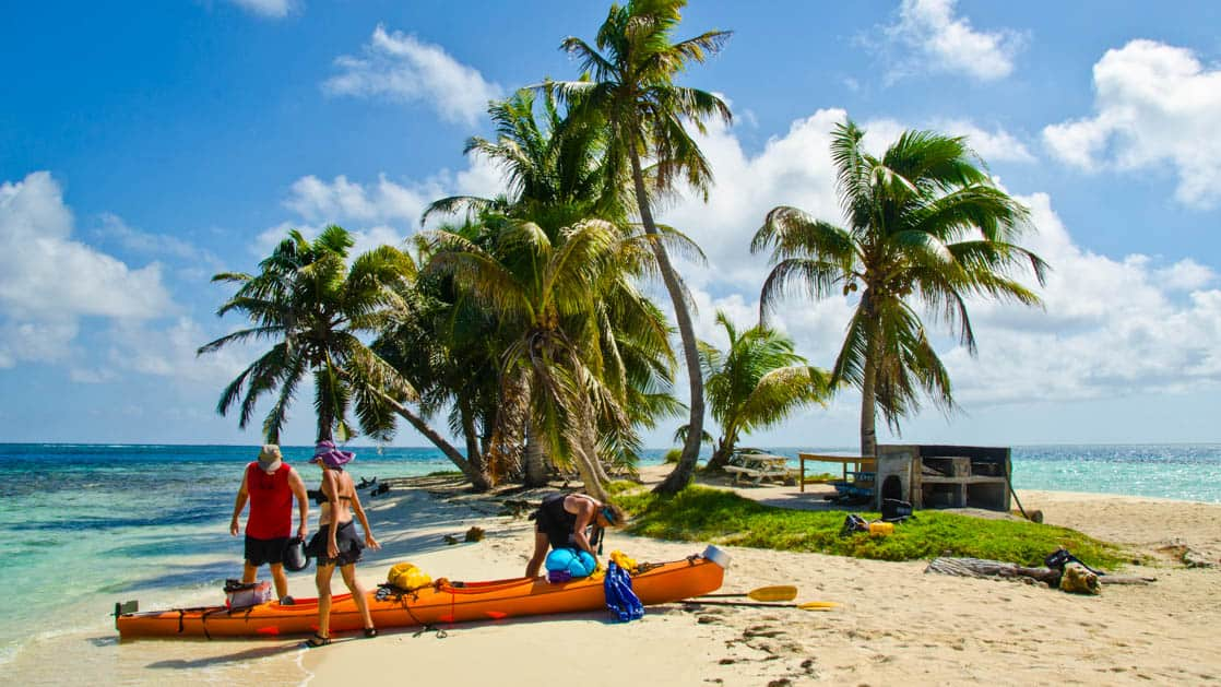 A couple gets instruction on efficient kayak packing on the Barrier reef island, Belize