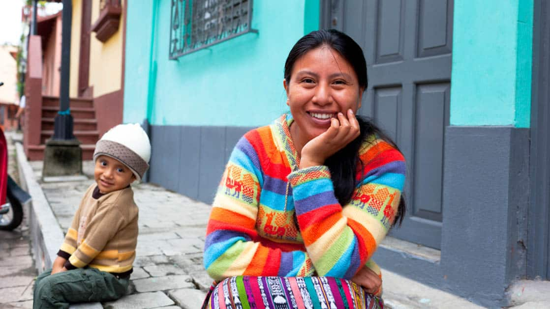 Guatemalan young mother and her son sitting on the sidewalk and smiling at the camera in Flores, Peten in Guatemala