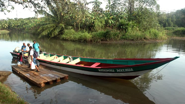 a large dugout canoe is tied to a small pier on a river while adventure travelers step out of it to start the best of panama land tour