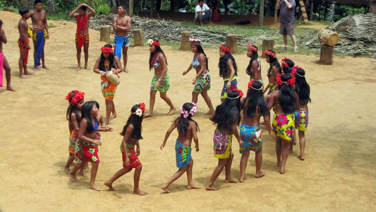 a group of indigenous women walk in a circle performing a traditional dance while men watch during the best of panama land tour