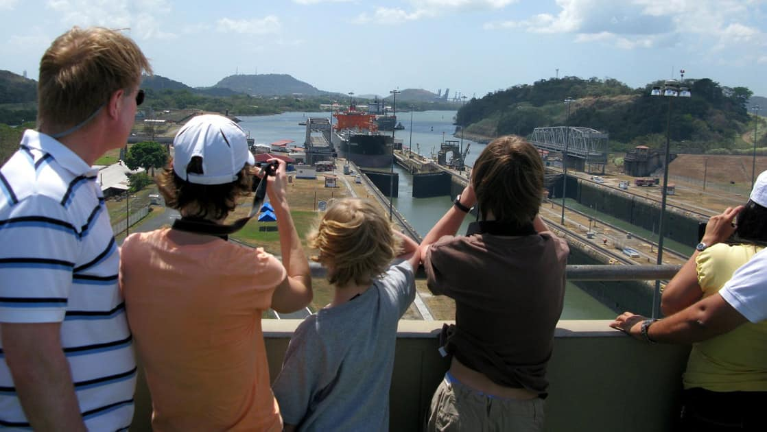 a family watches and takes pictures atop the miraflores locks on a sunny day during the best of panama land tour