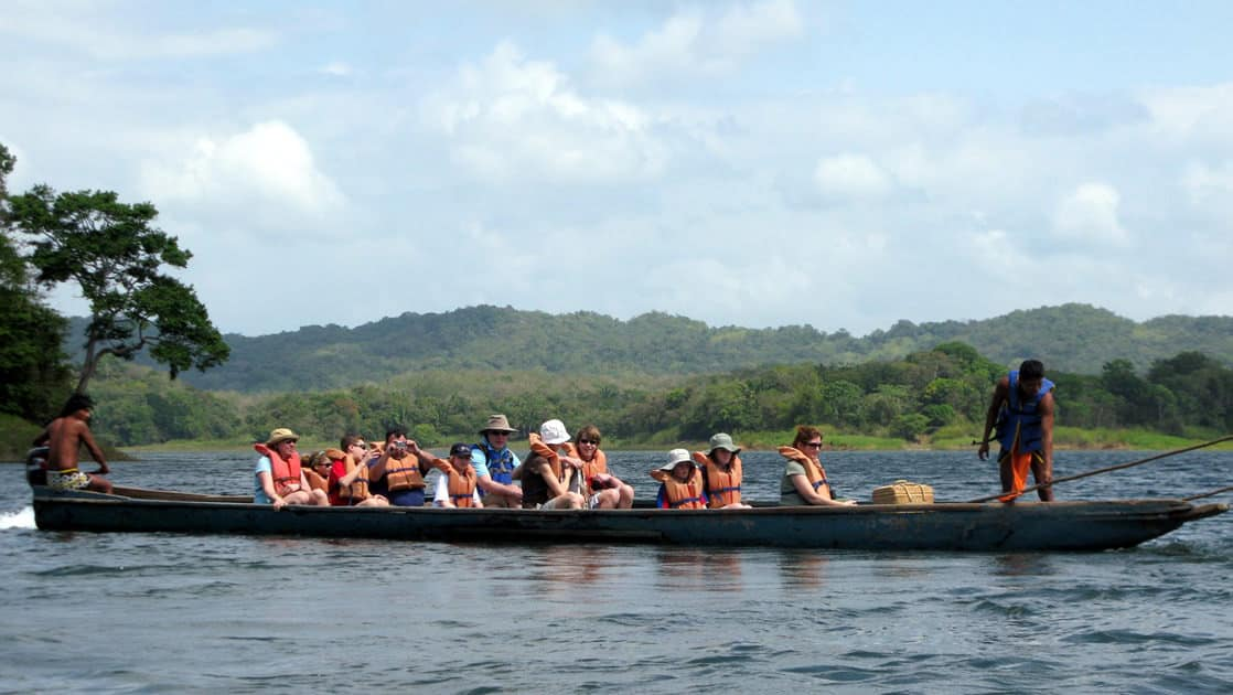 a group of adventure travelers rows a dugout canoe on flat water with mountains in the background on a sunny day during the best of panama land tour