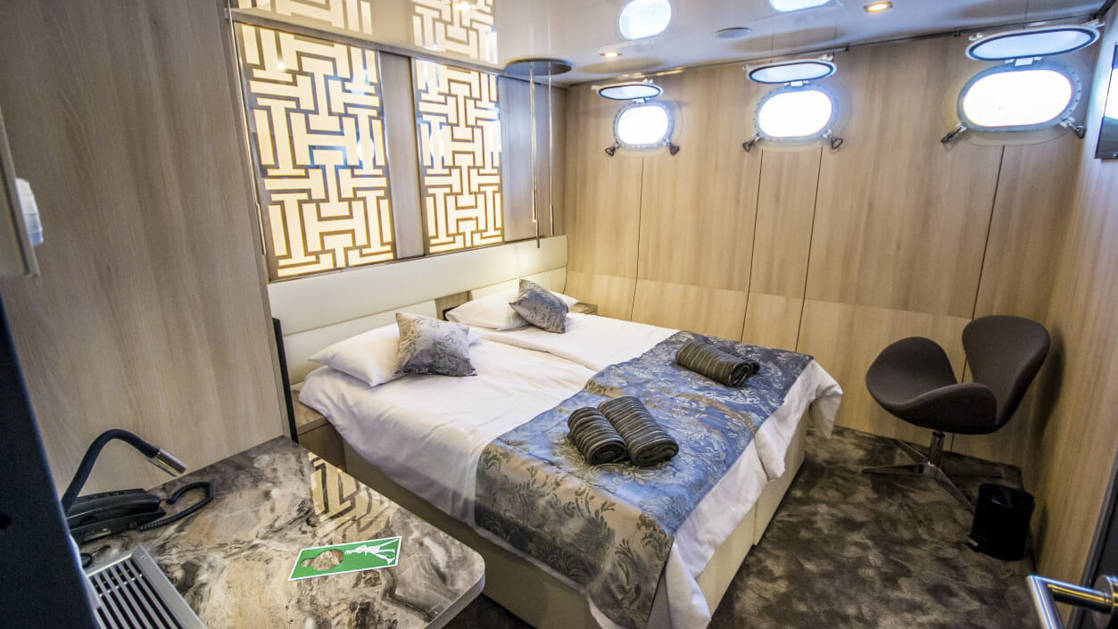 Lower Deck cabin aboard Black Swan with two beds together and three portholes.