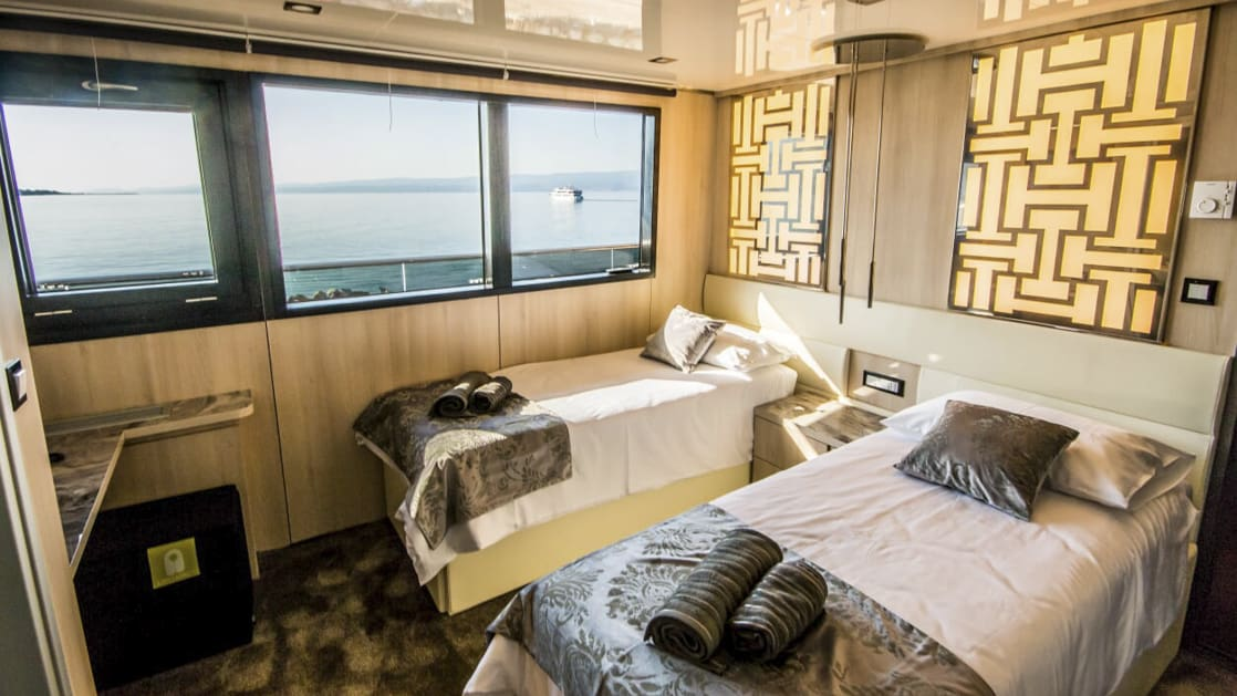 Main Deck Cabin aboard Black Swan with two twin beds and large windows.