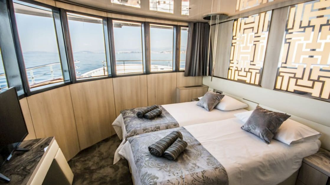 VIP Upper Deck cabin aboard Black Swan with large windows and beds together.