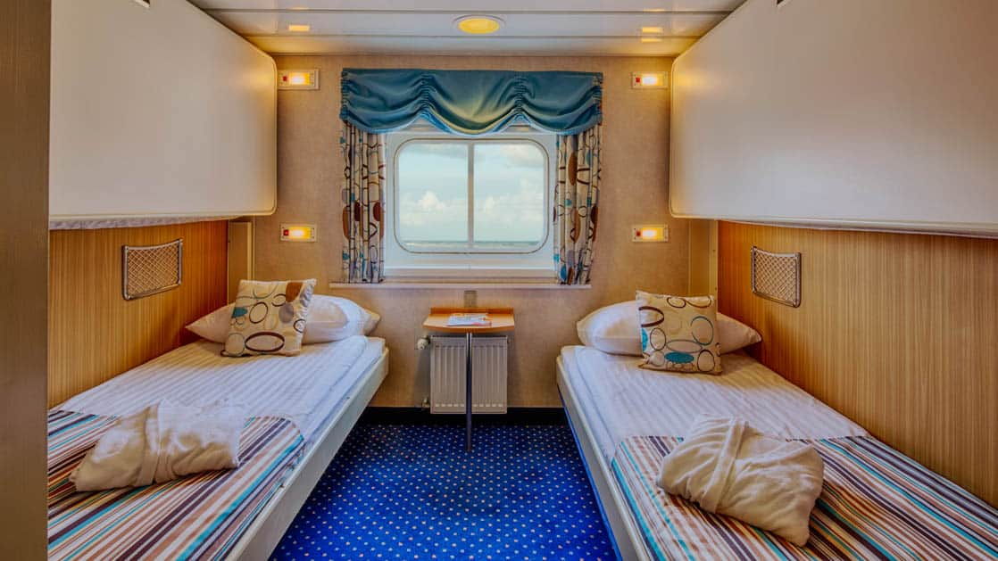 ocean nova quark cabin with 2 beds and a window centered between them